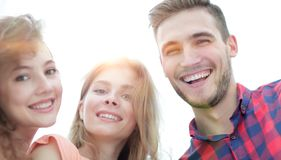 Closeup of three young people smiling on white background. Closeup of three happy young people smiling over white background Stock Photos