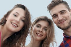 Closeup of three young people smiling on white background. Closeup of three happy young people smiling over white background Royalty Free Stock Images