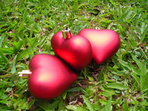 Closeup Of Three Hearts. Closeup of two hearts made of christmas decoration separated by a third heart in the middle of them symbolising third party intrusion Royalty Free Stock Images