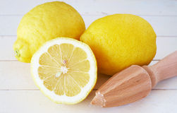 Closeup of three lemons and lemon juicer on white Royalty Free Stock Images