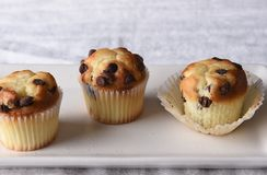 Closeup of three mini chocolate chip muffins on a white serving plate and a linen towel stock photo