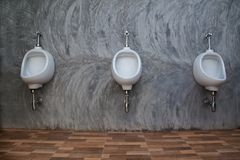 Closeup of three white urinals in men`s bathroom design of white Stock Photography