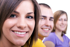 Closeup of three young people. Smiling on white background Stock Photos