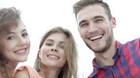 Closeup of three young people smiling on white background Stock Photos