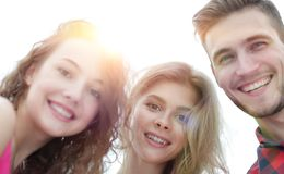 Closeup of three young people smiling on white background. Closeup of three happy young people smiling over white background Stock Photo