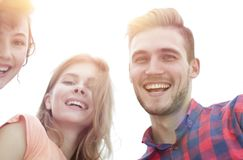 Closeup of three young people smiling on white background. Closeup of three happy young people smiling over white background Stock Photography