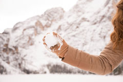 Closeup on throwing snowball woman among snow-capped mountains Stock Photography