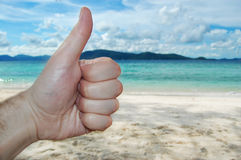 Closeup thumbs up on the beach background blue sky Royalty Free Stock Photography