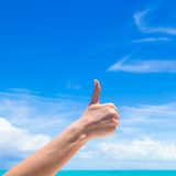 Closeup thumbs up on the beach background blue sky Stock Photo