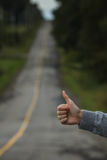 Closeup of a Thumbs up of a Caucasian Woman Hitchhiking. And Blurry Road in Background royalty free stock image