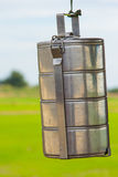 Closeup tiffin carrier on green field background Stock Images
