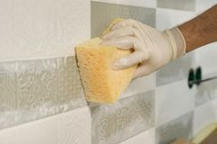 Closeup of tiler hand rubbing tile, Installing and grouting decorative finishes in environments with an high aesthetic value. Two- stock photo