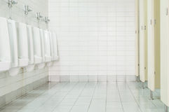 Closeup tiles wall in the toilet of man with toilet view by urinals and small room , interior at the old toilet background Stock Image