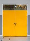 Closeup till den låsta dörren för gul metall med det Glass fönstret Arkivbild