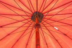 Closeup till det orange röda paraplyet för under-bambu arkivfoto