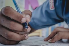 Closeup till handen av den hållande pennan för student och taexamen i classr royaltyfri fotografi