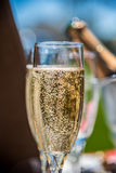 Closeup of tiny champagne bubbles in glass on sunny day Royalty Free Stock Images