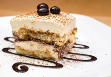 Tiramisu cake and chocolate swirl on white plate. Closeup of tiramisu cake and chocolate swirl on white plate Stock Photo