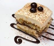Tiramisu cake and chocolate swirl on white plate. Closeup of tiramisu cake and chocolate swirl on white plate Stock Image