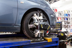 Closeup of tire clamped with aligner undergoing auto wheel align Stock Photography