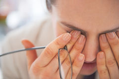 Closeup on tired business woman with eyeglasses. Closing eyes Royalty Free Stock Photo