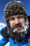 Closeup of  tired man with snow on his beard wearing winter hat Royalty Free Stock Photography