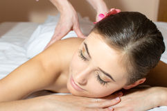 Closeup on tired pretty woman lying on a table and having fun taking beauty massages Stock Photo