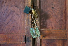 Closeup to Black and Yellow Padlock and Chain on Wood Door Royalty Free Stock Image