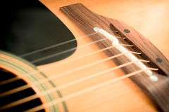 Closeup to bridge of acoustic guitar Royalty Free Stock Photography