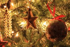 Closeup to Christmas decorations hanging on Christmas tree. Christmas tree debris immersed between branches and lit by Christmas lights Royalty Free Stock Photos