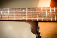 Closeup to fingerboard of acoustic guitar with softfocus backgro Royalty Free Stock Photos