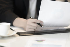Closeup to hand business woman hold pen and financial document Stock Photos