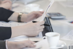 Closeup to hand business woman hold pen and financial document Royalty Free Stock Photo