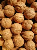 Walnuts. Closeup to lots of Walnut kernels and whole walnuts .Full background Royalty Free Stock Images