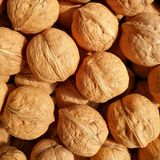 Walnuts. Closeup to lots of Walnut kernels and whole walnuts .Full background Royalty Free Stock Photo