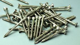 Heap of countersunk screws. Closeup to metal screws with flat heads lying on gray worktop Royalty Free Stock Photos