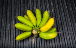 Closeup to Raw Bananas on Black Wavy Fiberglass Background Stock Images