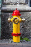 A closeup to a red and yellow fire hydrant Stock Photography