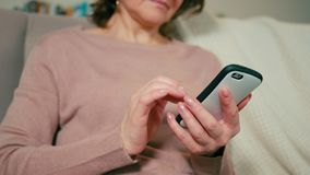 Closeup to smartphone in hands of a nice adult lady sitting on sofa with blanket. Closeup to smartphone in hands of a nice adult woman sitting on sofa in a cozy stock footage
