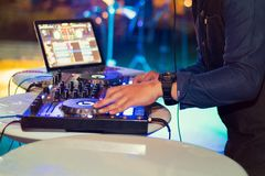 Dj mixes the track in party film tone with grain. Closeup to subject for more see detail stock photography