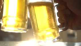 Closeup toast clinking lager beer glasses mugs with sun rays. Closeup toast clinking fresh lager beer glasses mugs with sun rays in hot summer day - video in stock video