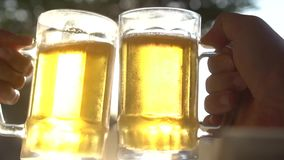 Closeup toast clinking lager beer glasses mugs with sun rays. Closeup toast clinking fresh lager beer glasses mugs with sun rays in hot summer day - video in stock footage