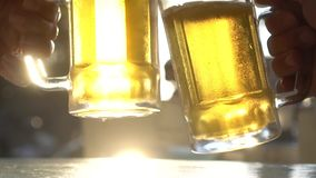 Closeup toast clinking lager beer glasses mugs with sun rays. Closeup toast clinking fresh lager beer glasses mugs with sun rays in hot summer day - video in stock video footage