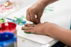 Closeup of toddler making palm print on paper Stock Photo