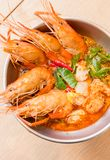 Closeup Tom Yum Goong. Tom Yum Goong Thai hot spicy soup shrimp with lemon grass,lemon,galangal and chilli on wooden background Thailand Food Royalty Free Stock Photography