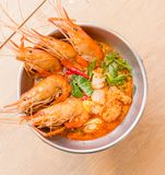 Closeup Tom Yum Goong. Tom Yum Goong Thai hot spicy soup shrimp with lemon grass,lemon,galangal and chilli on wooden background Thailand Food Stock Photography