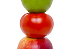 Closeup tomato which has green apple on top, and red apple in bottom on white background. Royalty Free Stock Photos