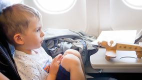 Closeup toned photo of cute toddler boy sitting in airplane and looking on small toy biplane stock photography