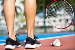 Athletic woman playing badminton on the court outside. Closeup of toned legs with a badminton racket and birdie stock image
