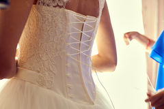 Closeup toned photo of beautiful bride tying up her wedding dress Royalty Free Stock Image